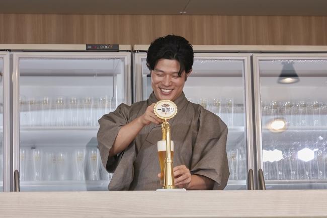 「一番搾り」のビアサーブをする鈴木さん