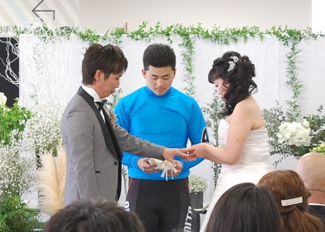 けいリングボーイ(別府けいりん篠田樹選手)が指輪の交換をサポート