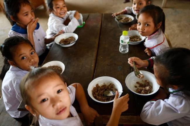 ラオス人民民主共和国サイ地区のバンボル小学校で地元の小学生が食事をする様子。
