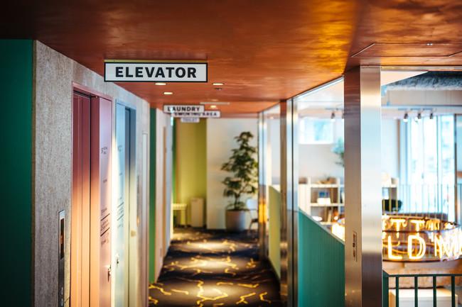 街の温度を写す色彩の 2階エレベーターホール
