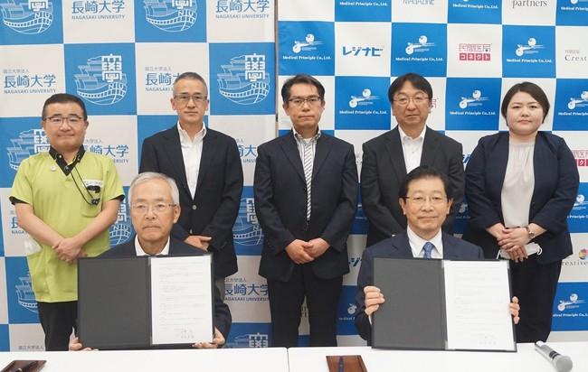 長崎大学で行われた協定締結式 (中央左:長崎大学 河野 茂 学長、右:MP社 由良芳從 社長)