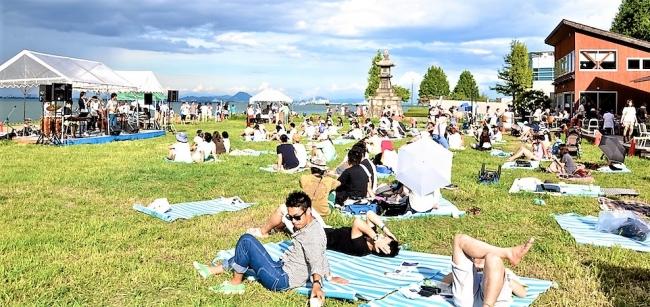 芝生で寝ころびながら音楽と風景を楽しむ