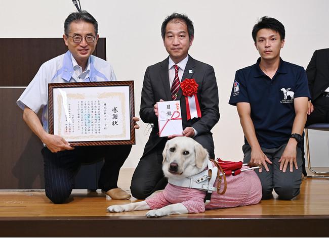 写真左:弊社代表取締役社長 小澤 素生、写真中央・右:中部盲導犬協会の方々とエーデル号