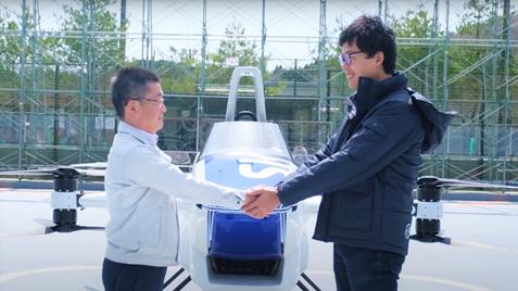 SkyDrive「空飛ぶクルマ」の前で握手する 三栄工業 代表取締役社長 神谷(左)とSkyDrive 代表取締役CEO 福澤(右)