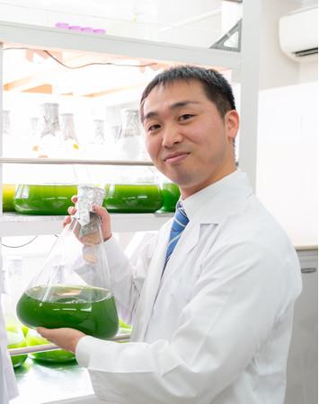 培養中の温泉微生物「RG92」を手に持つサラビオの宮田光義 中央研究所所長