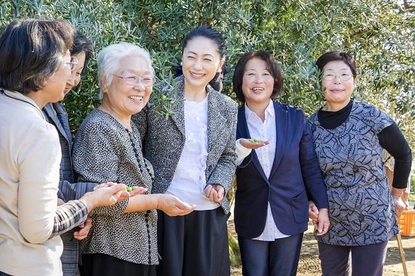 島外から嫁いできた女性参加者と談笑しながらオリーブを収穫する石川さゆりさん