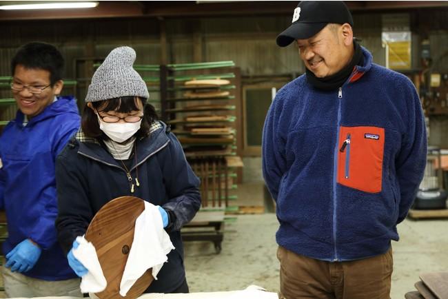 工場では若い女性職人も活躍している。右で微笑むのは伝統工芸株式会社 代表取締役 服巻俊彦さん。