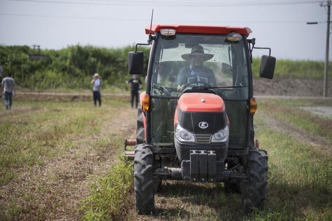 トラクターで耕起作業する孫泰蔵氏