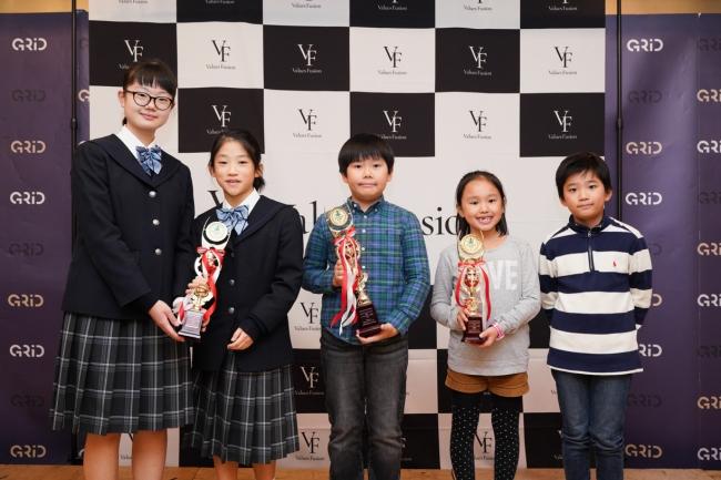 ソーシャルイノベーション部門の受賞者。左から優秀賞の中野 愛子さんと與語 泉さんのチーム(小6)、 大賞の小助川 晴大さん(小5)、特別賞の上田 夢さん(小2)、奮闘賞の出野 晴さん(小4)