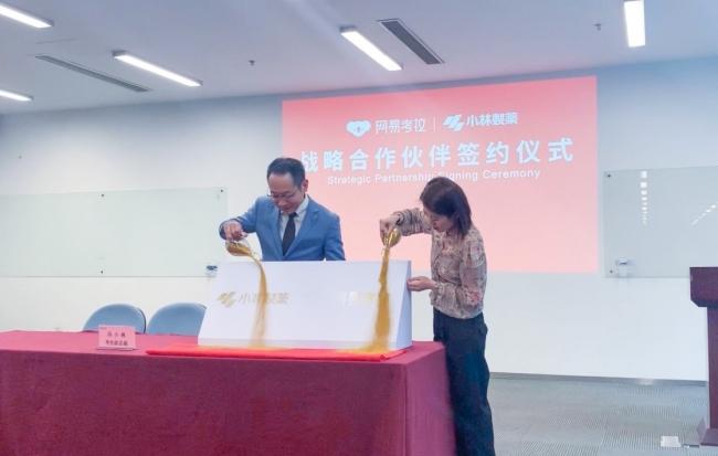 紀本信一郎氏と馮小楓氏が二社ロゴを刻んだ記念砂絵を完成させる