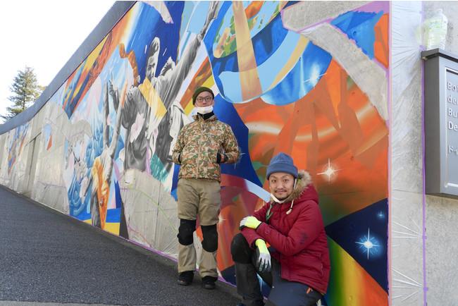 壁画の政治セクションの前に立つアーティストユニット「WHOLE9」のhitch氏とsimo氏