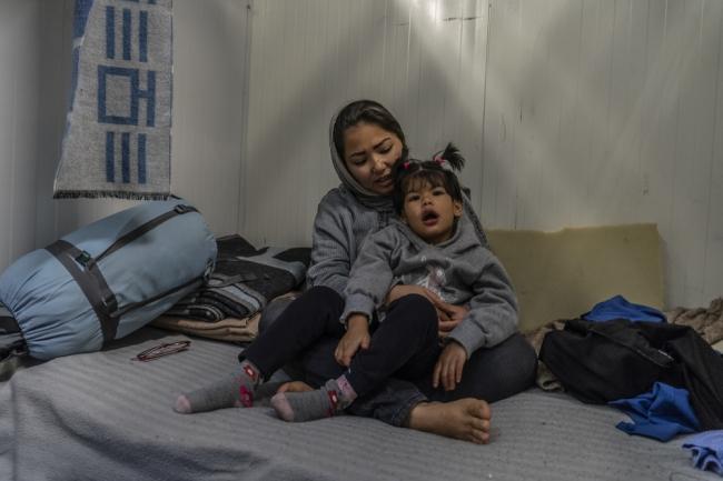 自閉症のある娘のザーラを抱っこするシャムセイェーさん (C) Anna Pantelia/MSF