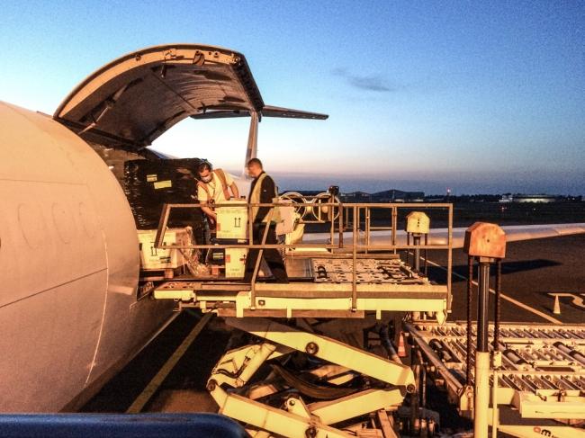 エアーテント式治療ユニットを含む医療用品を飛行機に積み込むMSFスタッフ(フランス・ボルドー) (c) Brigitte Rossotti MSF