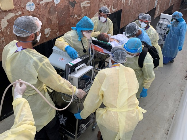 イエメン南部アデンの病院で新型コロナ重症患者を集中治療室へ移すMSFのスタッフ=2020年6月19日撮影 (C) Jacob Burns/MSF