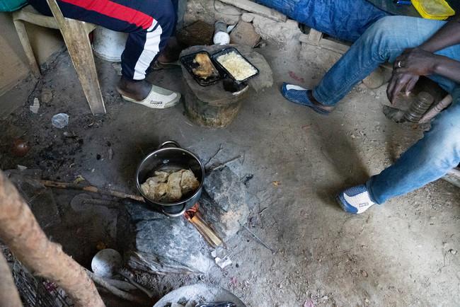 ホットスポットで配給された食事を温める男性たち (C) Evgenia Chorou