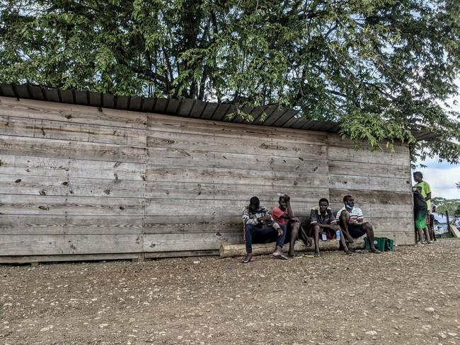 MSFが活動するラハス・ブランカス移民受入センターの前で座り込む移民 (C) Marcos Tamariz/MSF