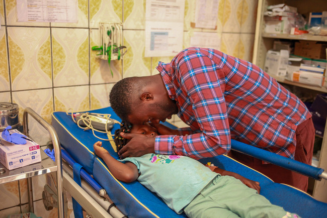 カメルーン北西州の病院で足の治療を受ける少女とその父親=2020年11月 (C) MSF/Scott Hamilton
