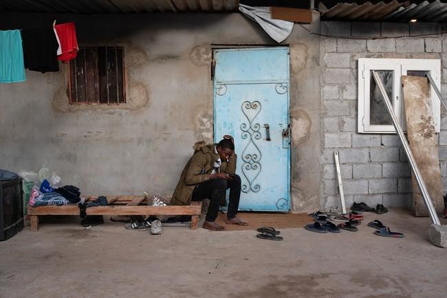 スーダンのダルフールから来た17歳の難民の男性。逮捕され、収容センターから逃げようとして両足を骨折し、その後は看守に激しく殴られたと言う。その日以来、働くことはおろか靴を履くこともできない=2020年1月 (C) Giulio Piscitelli