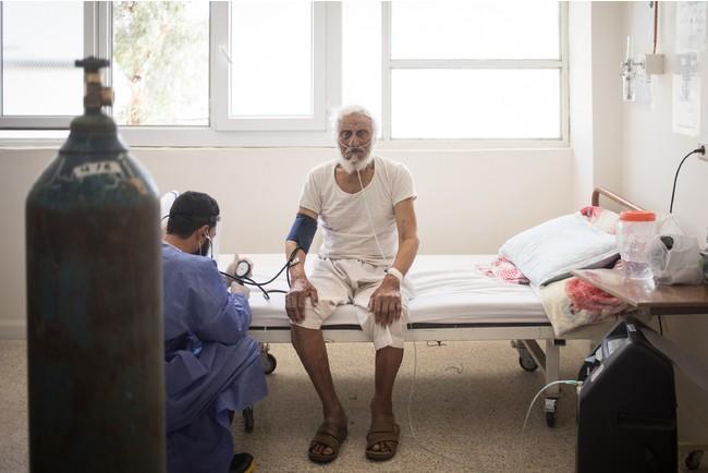 ラッカ国立病院に入院した60代のアブ・バクルさん。感染後、村の薬剤師を受診し一時悪化したが、その後適切な治療を受けて快復した=2021年6月 (C) Florent Vergnes