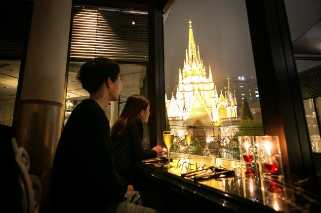 大きな窓からライトアップされた「青山セントグレース大聖堂」の夜景を臨める店内