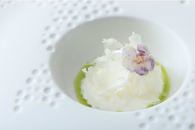 """純粋な村娘""""ラ・ベル""""をイメージ。春菊のオイルで香りづけされたホワイトアスパラのババロアと、純白のカリフラワーの前菜。"""