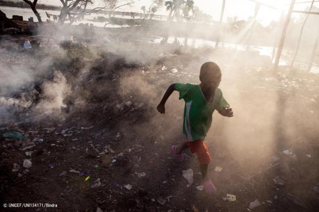 ごみを燃やす煙の中を走る男の子。(マリ)2012年12月撮影(C) UNICEF_UNI134171_Bindra