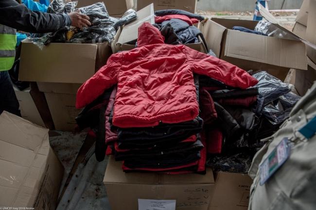 ユニセフは毎年、難民や国内避難民の子どもたちに冬用衣料などを支援している。写真は2018年2月にイラク北部のバシルマ難民キャンプの子どもたちに提供した衣服。(C) UNICEF_UN0162513_Anmar