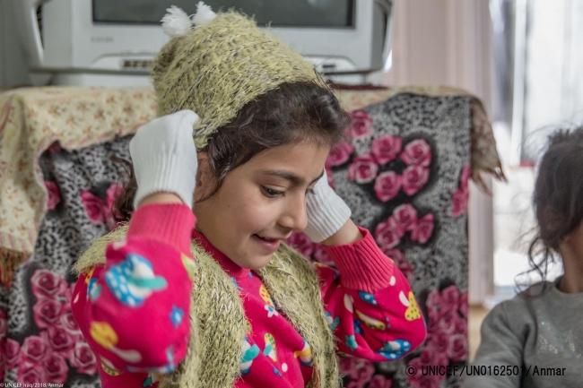 冬用の帽子や服を受け取った子ども(2018年2月撮影)。ユニセフは毎年、難民や国内避難民の子どもたちに冬用衣料などを支援している。(C) UNICEF_UN0162501_Anmar