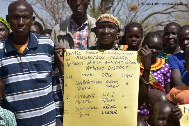 ウガンダの村で行われたFGM根絶のための啓発キャンペーンで、ポスターを持つ元施術者とコミュニティーの子どもたち。(2017年9月撮影) (C) UNICEF_UN0120218_Nakibuuka