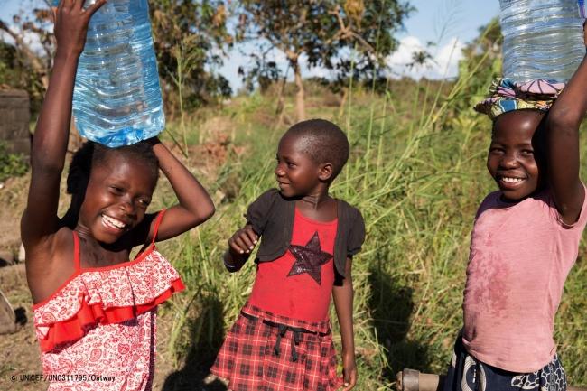 きれいな水を嬉しそうに運ぶ、避難生活を送る子どもたち。(C) UNICEF_UN0311795_Oatway