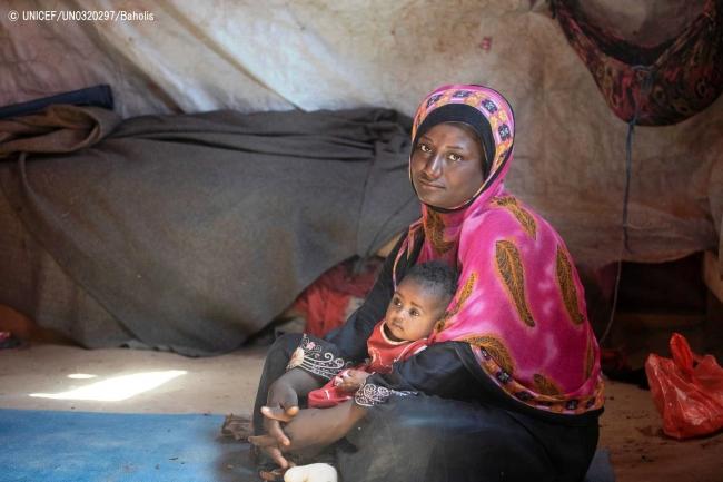 イエメン南部ラヒジュ県の国内避難民キャンプで、生後4カ月の娘を抱く母親。(2019年2月撮影) (C) UNICEF_UN0320297_Baholis