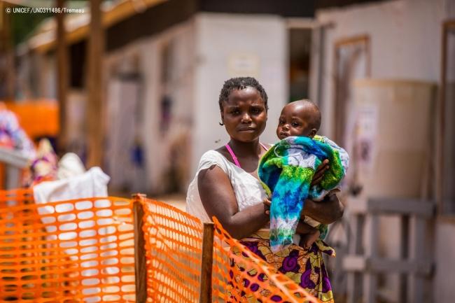 コンゴ民主共和国・ブテンボのエボラ治療センターで、生後10カ月の息子を抱く母親。(2019年3月撮影) (C) UNICEF_UN0311486_Tremeau