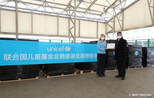 上海浦東国際空港でユニセフ・中国事務所代表から政府代表者へ医療従事者向けの支援物資を受け渡す様子。(2020年3月1日撮影) (C) UNICEF_UNI307634_