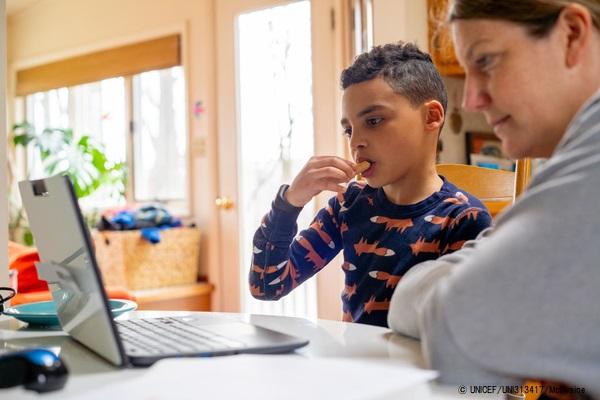 お菓子を食べながら遠隔授業の課題に取り組む8歳のルカくん。ルカくんの通う米国・コネチカット州の小学校は、13日から臨時休校となっている。(2020年3月20日撮影) (C) UNICEF_UNI313417_McIlwaine