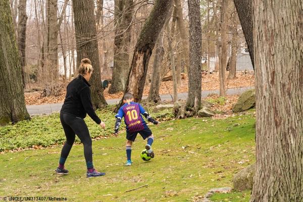 米国・コルチカット州で、遠隔授業の合間に母親とサッカーをする男の子。(2020年3月19日撮影) (C) UNICEF_UNI313407_McIlwaine