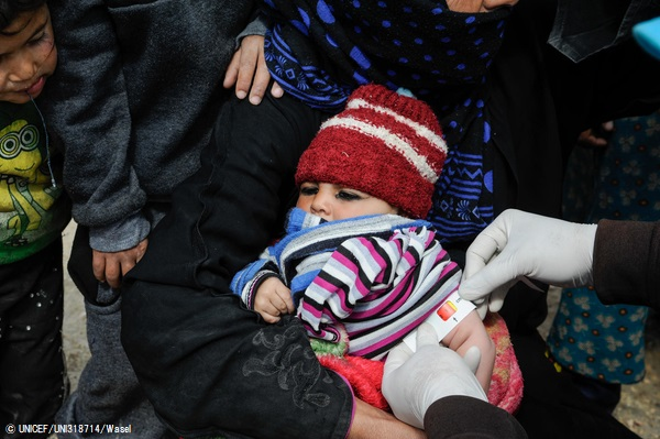 シリア・ラッカにあるMahmoudliキャンプで、上腕計測メジャーを使い栄養不良の検査を受ける赤ちゃん。(2020年3月29日撮影) (C) UNICEF_UNI318714_Wasel