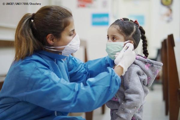 ベイルートのプライマリ・ヘルスケア・センターで、女の子の体温を計る看護師。(2020年4月3日撮影) (C) UNICEF_UNI317998_Choufany