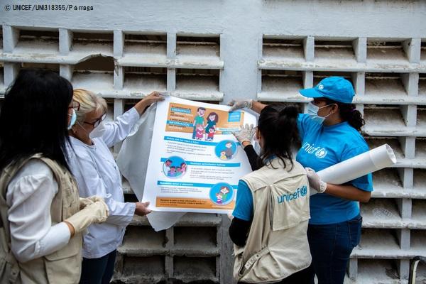 支援物資のポスターを広げて確認する様子。(2020年4月2日撮影) (C) UNICEF_UNI318355_Parraga