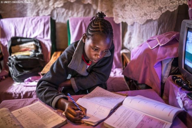 キベラの自宅で勉強するシェイラさん。週に一度、先生から両親の携帯電話に課題が届き、印刷して取り組んだ後、学校に送って先生に添削してもらう。(ケニア、2020年4月7日撮影) (C) UNICEF_UNI326279_Otieno