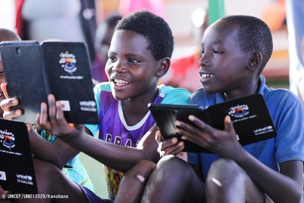 マハマ難民キャンプにある子どもにやさしい空間で、タブレットを用いたユニセフの学習プロジェクトの一環で教育アプリを使って遊ぶブルンジ難民の子どもたち。 (ルワンダ、2019年10月撮影) (C) UNICEF_UNI213329_Kanobana