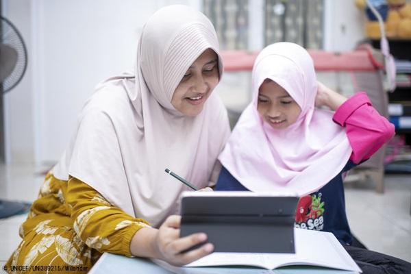 ボゴールの自宅で母親に手伝ってもらいながらオンライン学習をする8歳のジハンさん。(インドネシア、2020年9月26日撮影)© UNICEF_UNI389215_Wilander
