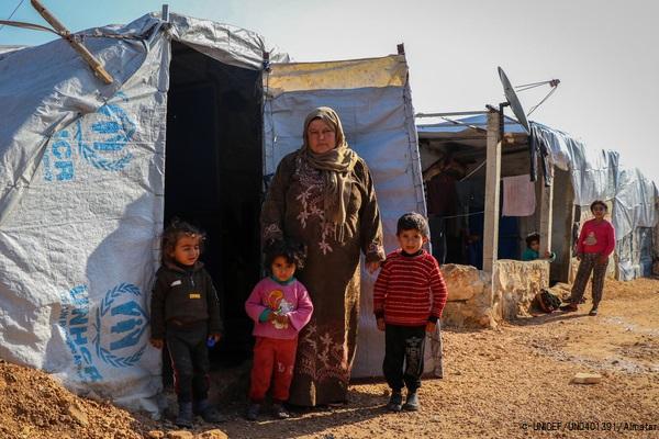 アレッポ県北部の農村部にある避難民キャンプで、テントの前に立つ家族。(2021年1月19日撮影) (C) UNICEF_UN0401391_Almatar