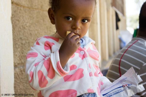 ティグライ州都メケレにある国内避難民キャンプで、高カロリービスケットを口にする2歳のメクリットちゃん。(2021年2月撮影) (C) UNICEF_UN0412579_Leul Kinfu