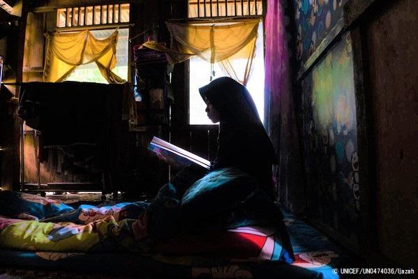南スラウェシ州の自宅で読書をする15歳のマーラさん(仮名)。休校によりオンライン学習に切り替わった中、男性より結婚の申し込みがあったが、勉強を続けるために断った。(インドネシア、2021年4月撮影) © UNICEF_UN0474036_Ijazah