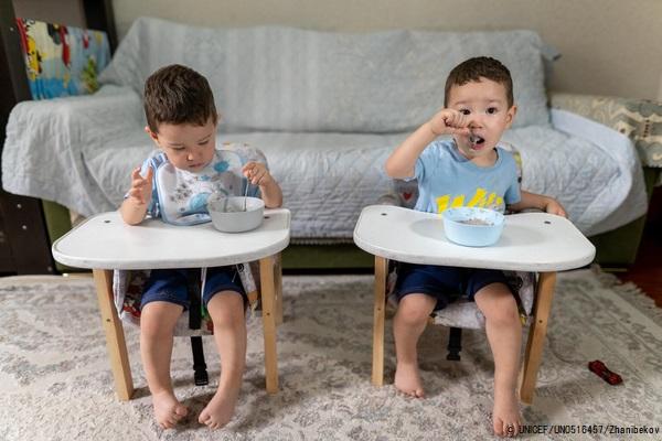 ビシュケクの自宅で、好物のお粥を食べる双子の1歳のアデルちゃんとアリムちゃん兄弟。(キルギス、2021年8月28日撮影) (C) UNICEF_UN0516457_Zhanibekov