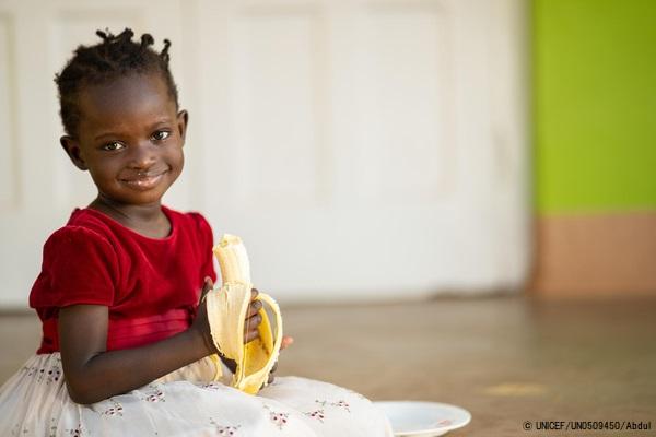 米や野菜など栄養価の高い昼食を取った後に、デザートのバナナを食べる3歳のエメラルドちゃん。(ウガンダ、2021年8月28日撮影) (C) UNICEF_UN0509450_Abdul