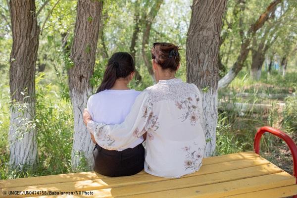 母親と一緒に公園のベンチに座る13歳のアイムさん(仮名)。3年前に自分は愛されていないと思い自殺を考えることもあったが、心理学者のカウンセリングを受け回復した。(カザフスタン、2021年5月撮影) (C) UNICEF_UN0474758_Babajanyan