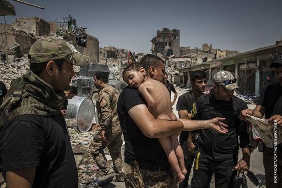 世界報道写真コンテスト 一般ニュースの部 組写真1位 イヴォール・プリケット(アイルランド) ニューヨークタイムズに提供、2017年7月12日 モスルをめぐる戦闘:イラク軍特殊部隊の兵士によって手当てをうける身元不明の男の子。
