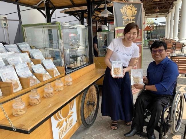 障がい者支援NGOが展開するお菓子やドライマンゴーを販売するお店の前で、原畑実央と、サミス氏。