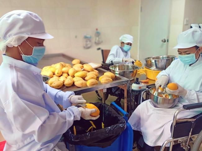 カンボジアの首都プノンペンにある工房にてドライマンゴーは手づくりされる。